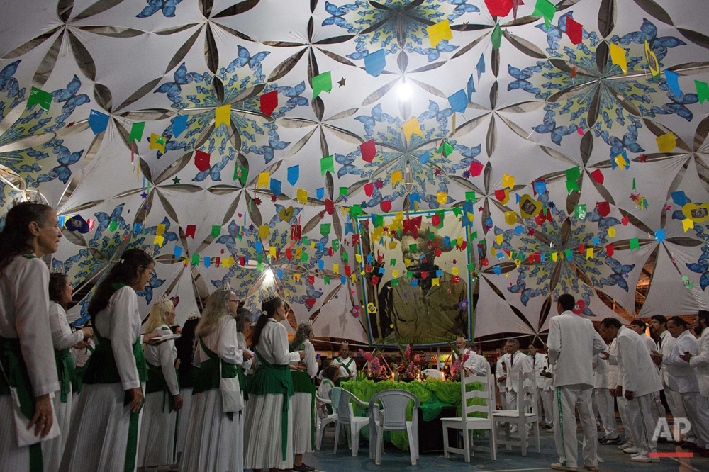 In this June 22, 2016 photo members of the church of the Holy Daime attend a service in honor of Saint John, in Ceu do Mapia, Amazonas state, Brazil. A photo of the founder of Santo Daime, Raimundo Irineu Serra, known as Mestre Irineu is displayed prominently in the background.(AP Photo/Eraldo Peres)