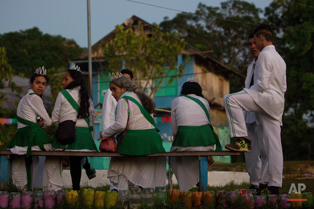 In this June 22, 2016 photo, members of the community mill around the local temple before partaking in the ritual Holy Daime in Ceu do Mapia, Amazonas state, Brazil. During the service men and women lined up in two separate rows to drink the psychedelic tea after making the sign of the cross. They then sing together prayers and psalms in a large circle. (AP Photo/Eraldo Peres)