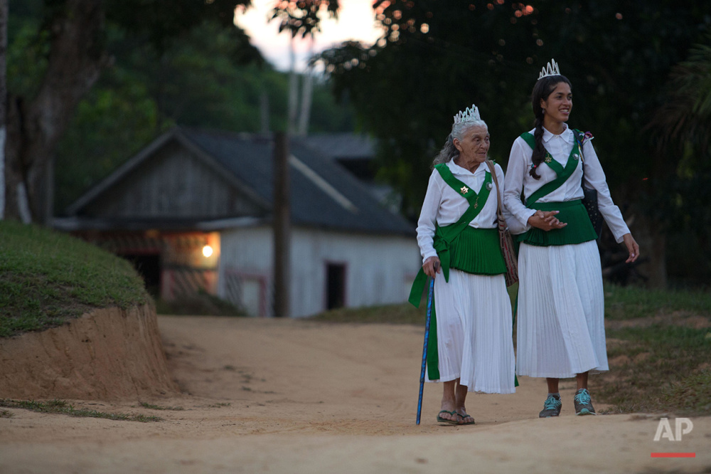 In this June 22, 2016 photo, 83-year-old Godmother Julia Chagas, left, walks supported by her granddaughter to attend the ritual of the Holy Daime in Ceu do Mapia, Amazonas state, Brazil. Chagas is the widow of rubber tapper Sebastiao Mota de Melo, nicknamed Godfather Sebastiao, the founder of the community. She still heads the sect with her two sons. (AP Photo/Eraldo Peres)