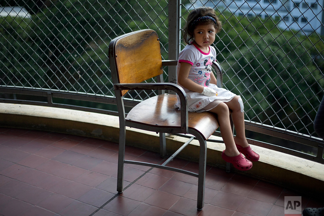 In this Aug. 16, 2016 photo, Ashley Pacheco sits in a chair on a balcony at University Hospital in Caracas, Venezuela. Two weeks after the 3-year-old scraped her knee, she was screaming in a hospital, fighting for her life as her family scoured Caracas for scarce antibiotics. (AP Photo/Ariana Cubillos)