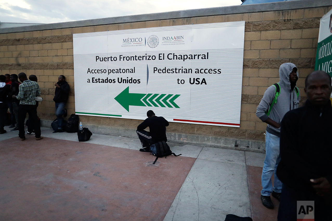 n this Sept. 27, 2016 photo, Haitian migrants wait at the border crossing in Tijuana, Mexico. Mexican officials distribute paper slips with dates to appear at San Ysidro on the U.S. side of the border. (AP Photo/Gregory Bull)