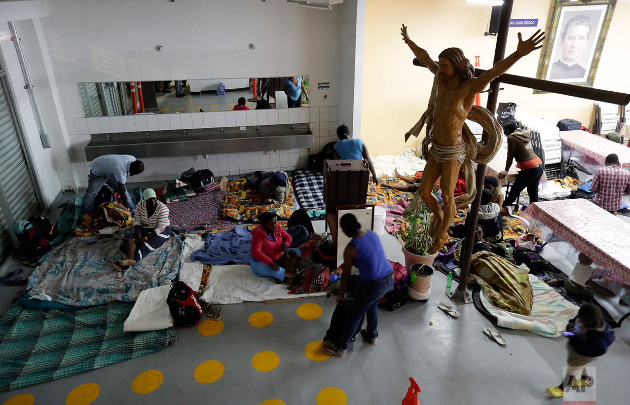 In this Oct. 3, 2016 photo, Haitian women and children get ready to sleep on the floor of the Padre Chava migrant shelter in Tijuana, Mexico. Hundreds, perhaps thousands, of Haitian men, women and children regularly spend the night just outside the busiest U.S. border crossing. (AP Photo/Gregory Bull)
