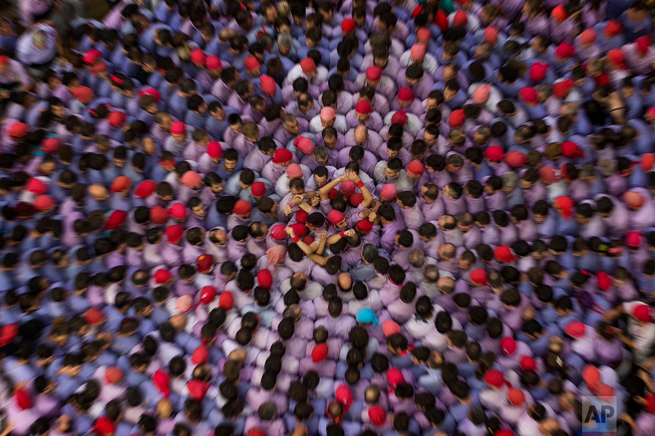 "In this Sunday, Oct. 2, 2016 photo, members of the Marrecs de Salt form the base to make their human tower during the 26th Human Tower Competition in Tarragona, Spain. The tradition of building human towers, or Castells, dates back to the 18th century and takes place during festivals in Catalonia. ""Colles,"" or teams, compete to build the tallest and most complicated towers. The structure of the castells varies depending on their complexity. (AP Photo/Emilio Morenatti)"