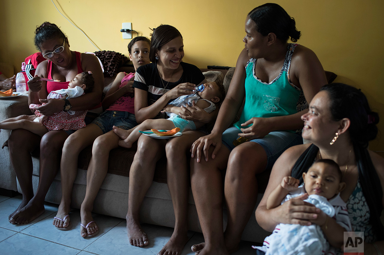 In this Oct. 1, 2016 photo, mothers hold their babies, who have microcephaly, from left, Alice Vitoria, Juan Pedro and Joao Guilherme, during Arthur's one-year birthday party, at his home in Recife, Pernambuco state, Brazil. Away from medical facilities, many of the mothers of babies born with microcephaly get together and try to keep a semblance of normalcy by celebrating milestones, like first birthdays. (AP Photo/Felipe Dana)