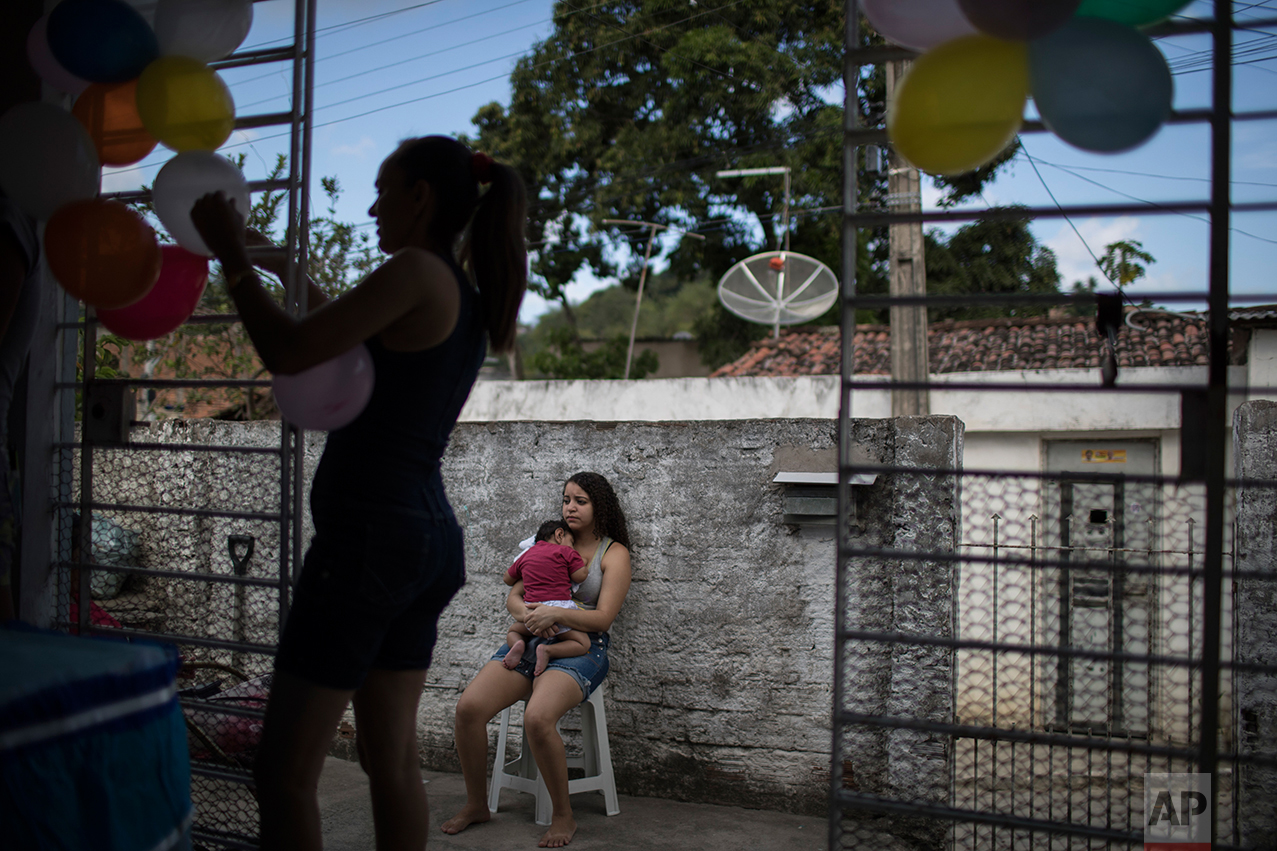 In this Oct. 1, 2016 photo, Tatiane holds her nephew Arthur Conceicao, who was born with microcephaly, during his one-year birthday party in Recife, Pernambuco state, Brazil. Health Minister Ricardo Barros said there was a drop of 85 percent in microcephaly cases in August and September compared to those months last year, when the first births started worrying pediatricians. He credited growing awareness of the virus and government attempts to combat mosquitoes through spraying campaigns. (AP Photo/Felipe Dana)