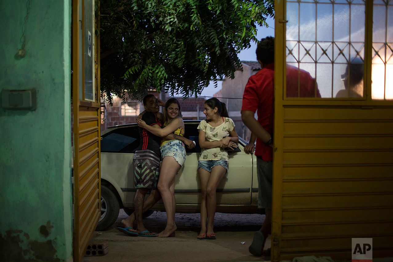 In this Sept. 26, 2016 photo, Angelica Pereira, center right, chats with her sister and sister's boyfriend outside her home as her infant daughter Luiza, who was born with microcephaly, sleeps in Santa Cruz do Capibaribe, Pernambuco state, Brazil. A year after a spike in the number of newborns with the defect known as microcephaly, doctors and researchers have seen many of the babies develop swallowing difficulties, epileptic seizures and vision and hearing problems. (AP Photo/Felipe Dana)