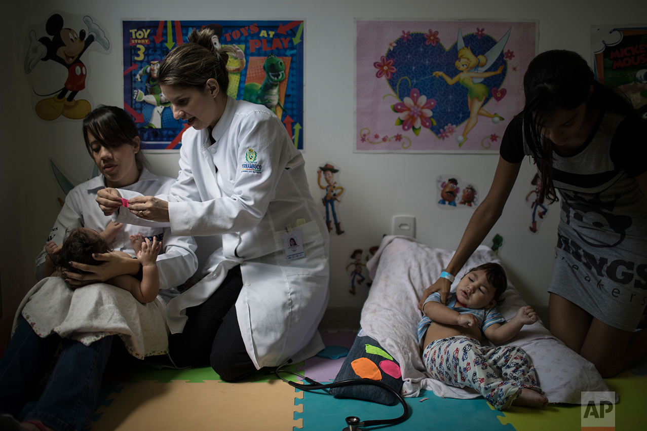 In this Sept. 27, 2016 photo, physical therapist Camilla Costa, left, and speech therapist Amora Marins apply Kinesio Tape on Luiza as Victoria Leticia, right, holds her son Lucas Matheus, during a physical therapy session for babies born with microcephaly at the UPAE hospital in Caruaru, Pernambuco state, Brazil. (AP Photo/Felipe Dana)