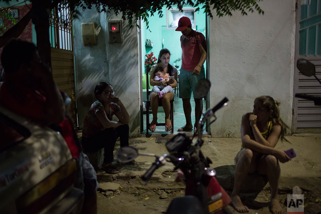 In this Sept. 26, 2016 photo, Angelica Pereira holds her daughter Luiza, who was born with microcephaly, as her husband Dejailson Arruda stands by at their home in Santa Cruz do Capibaribe, Pernambuco state, Brazil. Pereira says it's a victory just for her daughter Luiza to reach her first birthday. Despite Luiza's suffering from daily seizures and breathing problems, Pereira is hopeful her health and motor skills will improve with time. (AP Photo/Felipe Dana)