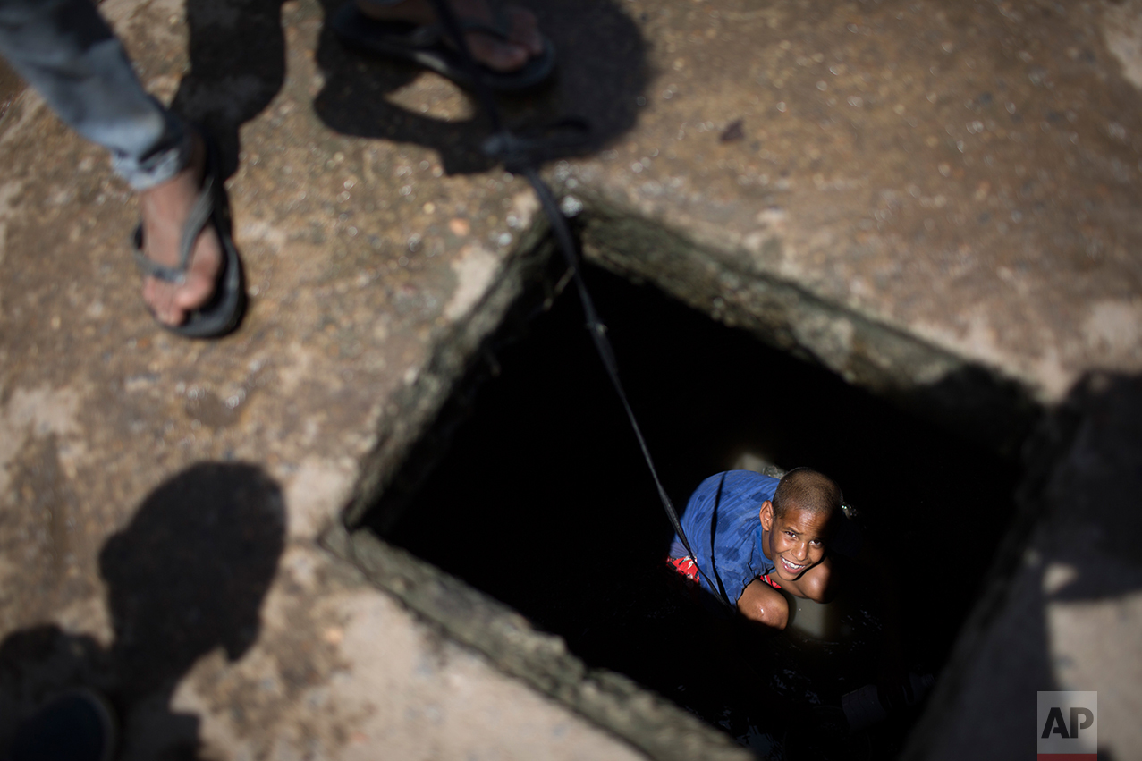 This Sept. 26, 2016 photo shows Lucas, 11, collecting water from a polluted well in a village near Caruaru, Pernambuco state, Brazil. Lucas' family uses the water for bathing, and for horses and donkeys to drink. One of the main reasons this region was so affected by Zika is the fact that they don't have water, so they collect and store water everywhere, creating a perfect breading site for mosquitoes, which carry the virus. (AP Photo/Felipe Dana)