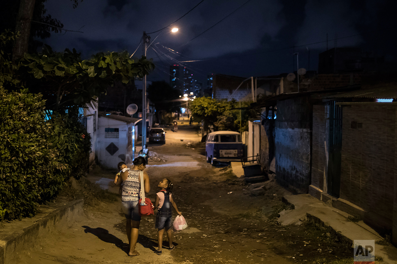 In this Oct. 1, 2016 photo, Vanessa dos Santos holds her son Enzo, who was born with microcephaly, as she walks home with her daughter Lorena in Recife, Pernambuco state, Brazil. Studies are underway to determine if the timing of mothers who were infected with Zika during pregnancy affects the severity of the abnormalities, said Ricardo Ximenes, a researcher at the Fiocruz Institute in Recife. (AP Photo/Felipe Dana)