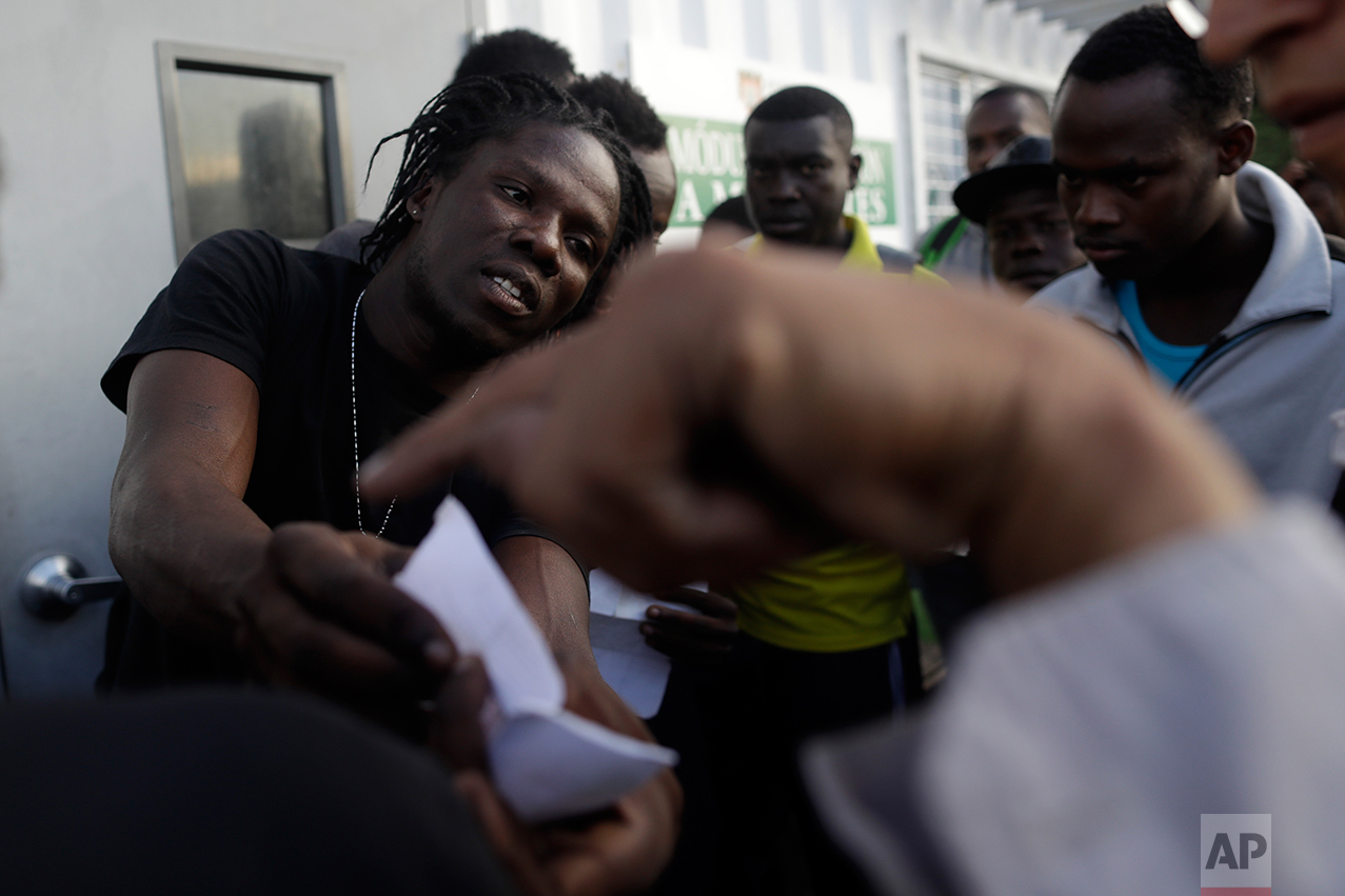 In this Sept. 27, 2016 photo, Haitian migrants speak with Mexican officials as they hope to gain a spot on the daily list to pass to the U.S. side of the border crossing, in Tijuana, Mexico. Once inside the United States, the Haitians cannot be returned back to Mexico. They are held in U.S. detention centers pending repatriation. (AP Photo/Gregory Bull)