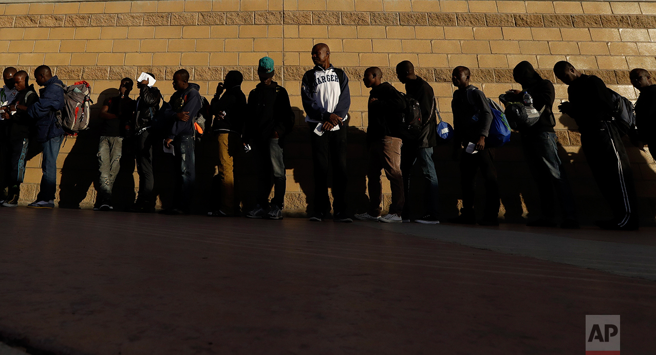 In this Sept. 2, 2016 photo, Haitian migrants line up as they wait to enter the U.S. border crossing, in Tijuana, Mexico. As the U.S. repatriate the migrants it has a limited number of beds at its immigration detention facilities to accommodate people while flights and travel documents are arranged. (AP Photo/Gregory Bull)