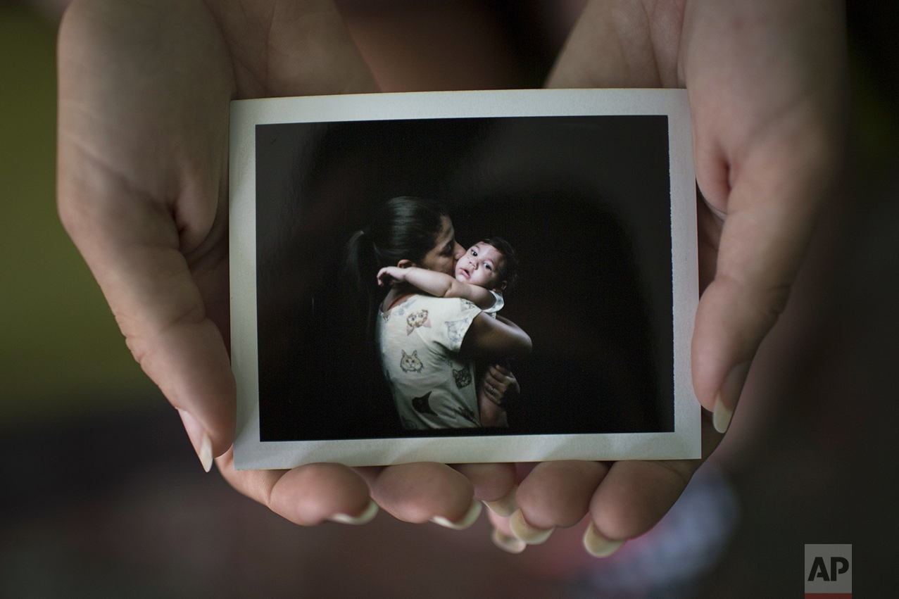 In this Sept. 26, 2016 photo, Angelica Pereira holds a instant film photo of her and her daughter Luiza, who was born with microcephaly, one of many serious medical problems that can be caused by congenital Zika syndrome, in Santa Cruz do Capibaribe, Pernambuco state, Brazil. For a brief moment, mothers with 1-year-old babies with microcephaly, forgot about getting that hard-to-find drug needed to prevent their babies from having seizures or the uncomfortable stares directed at their children born with small heads because of a Zika virus infection in the womb. Instead they were just like any other moms getting the first formal photographs of their babies. (AP Photo/Felipe Dana)