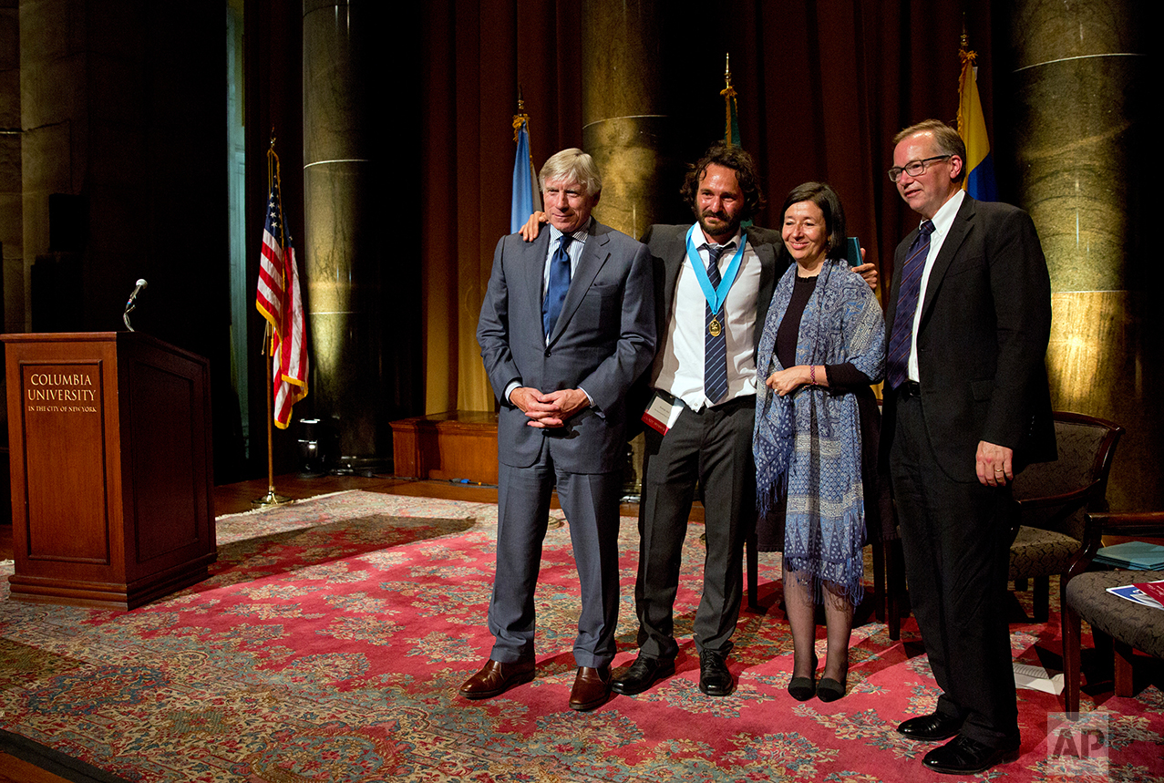 Photographer Rodrigo Abd of The Associated Press, second from left, poses for photos with Lee. C. Bollinger, President of Columbia University, left, Maria Teresa Ronderos, Chair of the Cabot board, second from right, and Steve Coll, Dean of Columbia's Journalism school during the Maria Moors Cabot Prize award ceremony at Columbia University in New York City, Tuesday Oct. 18, 2016. Abd and three other journalists in Brazil, Colombia and El Salvador received this year's Maria Moors Cabot Prize.(AP Photos/Enric Marti)