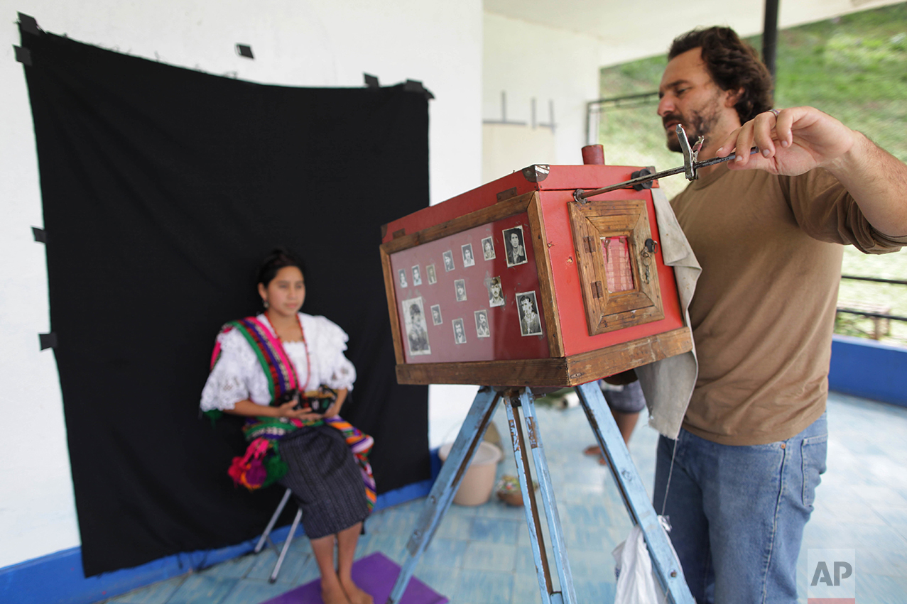 In this Aug. 8, 2011 photo, Associated Press photographer Rodrigo Abd uses a 19th-century style wooden box camera as he photographs a participant of the Rabin Ajau National Folkloric Festival in Guatemala City. Participants had to hold still for up to two minutes as Abd made exposures with light shining directly from the lens onto photo paper inside the box camera.  (AP Photo/Jesus Cuque Lopez)