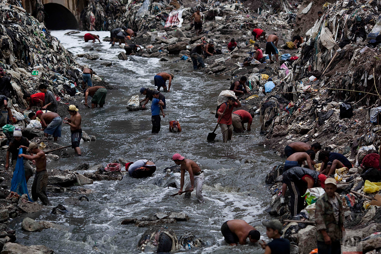 "In this Oct. 19, 2011 photo, people search for scrap metal in contaminated water at the bottom of one of the biggest trash dumps in the city, known as ""The Mine,"" in Guatemala City. (AP Photo/Rodrigo Abd)"