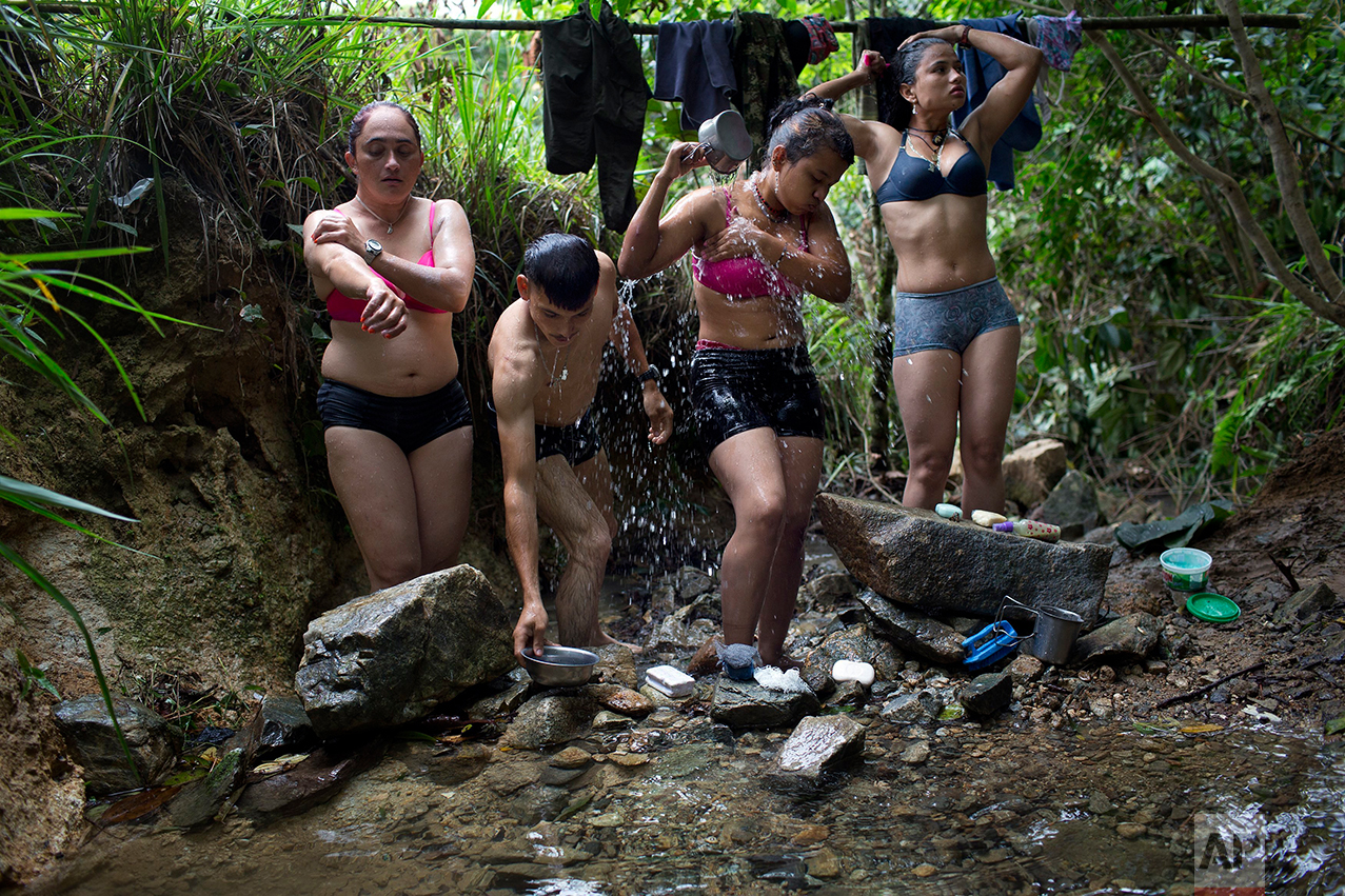 In this Jan. 4, 2016 photo, rebel fighters for the 36th Front of the Revolutionary Armed Forces of Colombia, or FARC, bathe in a creek near their hidden camp in Antioquia state, in the northwest Andes of Colombia. The rebel fighters share all facilities on equal terms. Many of them are couples and share sleeping quarters.  (AP Photo/Rodrigo Abd)