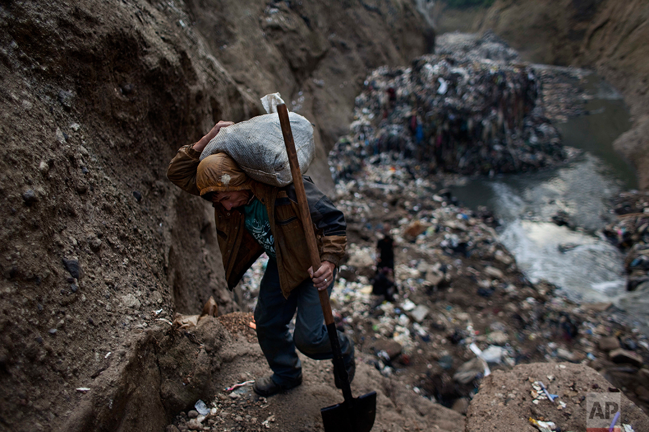 "In this Oct. 5, 2011 photo, a man who only gave his first name Wilmer carries a sack of metal he collected after working the entire day at the bottom of one of the biggest trash dumps in the city, known as ""The Mine,"" in Guatemala City. This activity known locally as ""mining"" is extremely dangerous due to mud slides and collapses, but earns many of them about 150 quetzals ($20 dollars) a day, nearly twice the minimum daily wage. (AP Photo/Rodrigo Abd)"