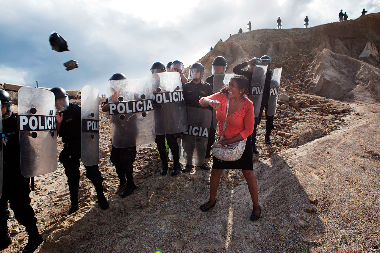 In this April 28, 2014 photo, a woman throws a rock and a bag at riot policemen who block her way home in Huepetuhe district in Peru's Madre de Dios region in Peru. Authorities began enforcing a ban on illegal mining in the Huepetuhe district, and before the deadline, miners clashed with police while intermittently blocking traffic on the Interoceanic Highway that links the Pacific with Brazil.  (AP Photo/Rodrigo Abd)