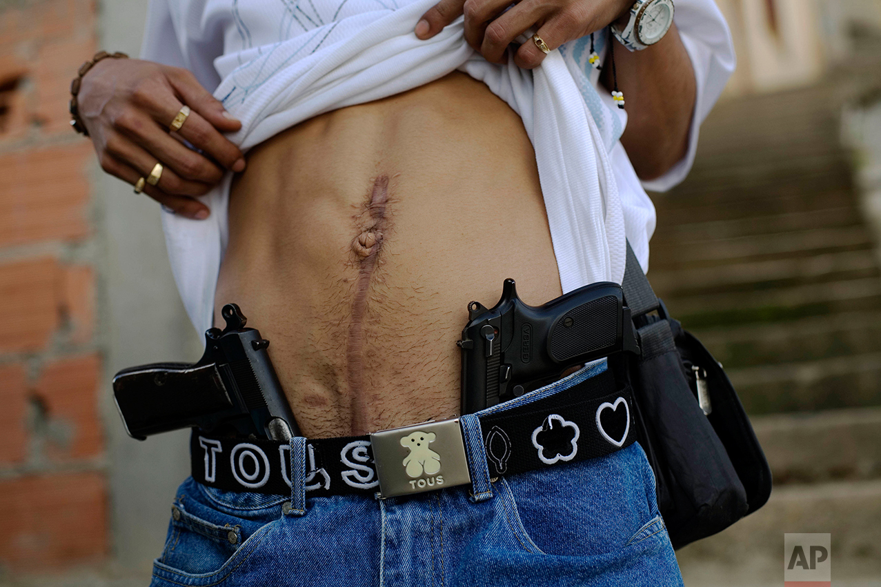 "In this Nov. 25, 2007 photo, drug dealer Joan, who identifies himself as ""El Patan,"" shows his guns and a scar on his stomach from an injury suffered during clashes with rival gangs in Las Mayas neighborhood in Caracas, Venezuela. (AP Photo/Rodrigo Abd)"