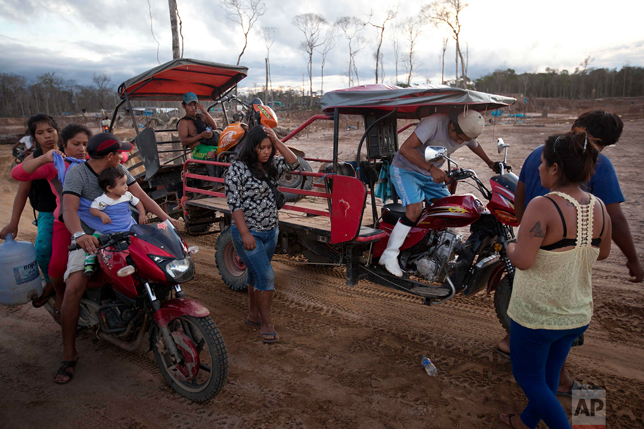 In this May 16, 2014 photo, miners leave the site where they lived and worked after police destroyed their illegal mining operation in La Pampa in the Madre de Dios region of Peru, Friday, May 16, 2014. Madre de Dios state has an estimated 40,000 illegal miners, most of whom are poor migrants from the Andean highlands.  (AP Photo/Rodrigo Abd)