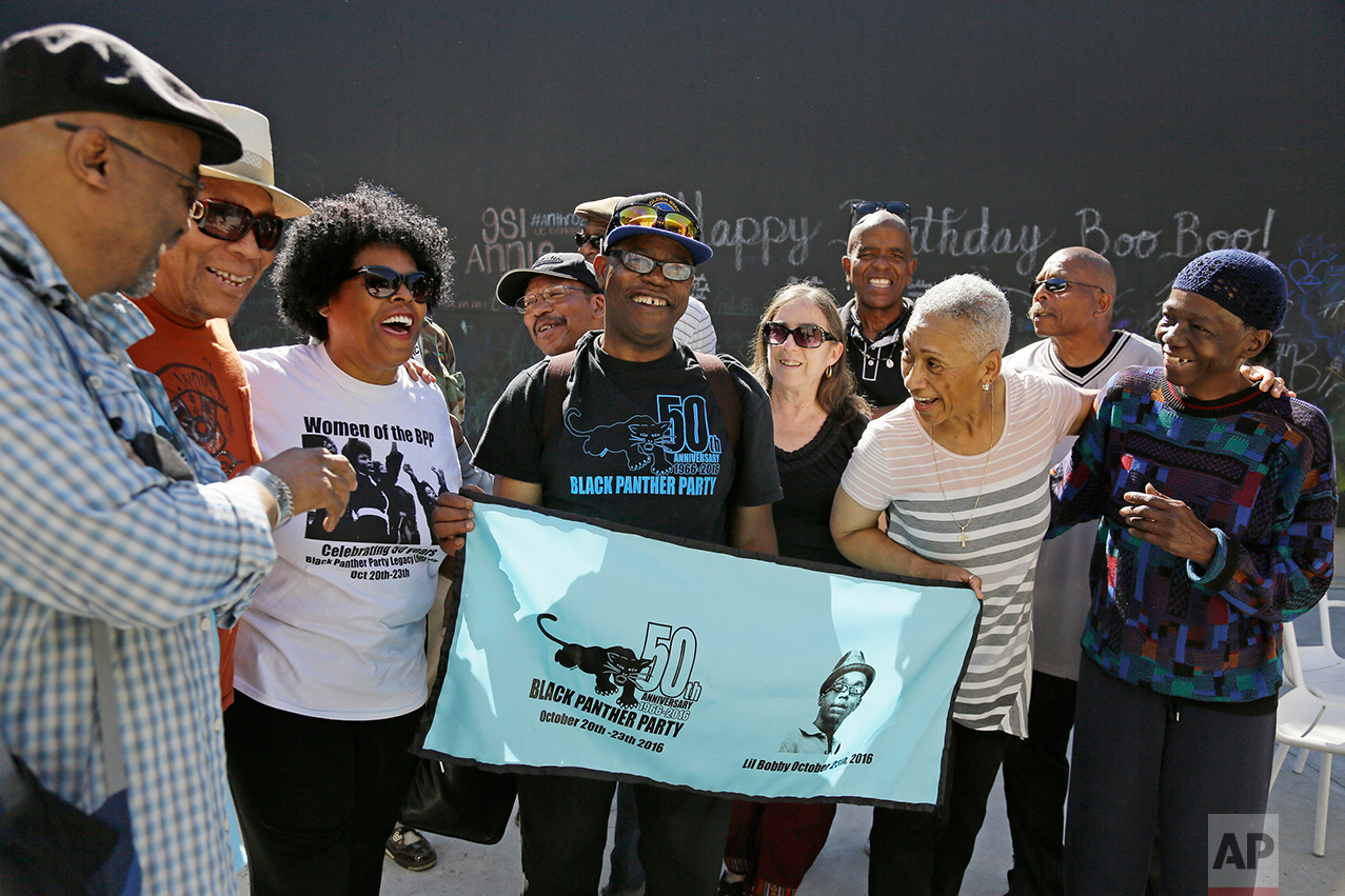 In this photo taken Saturday, Oct. 8, 2016, former members of the Black Panther Party laugh and visit outside a museum after an anniversary meeting in Oakland, Calif. In the front row is Billy X. Jennings, center, M. Gayle Asali-Dickson, second from right and Lorene Johnson, right. (AP Photo/Eric Risberg)