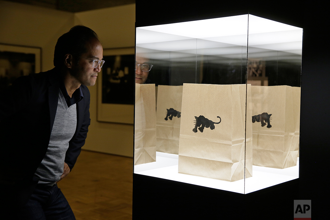 """In this photo taken Monday, Oct. 3, 2016, senior curator Rene de Guzman looks over a bag used by the Black Panther Party to give away food in the exhibition called """"All Power to the People: Black Panthers at 50"""" at the Oakland Museum of California in Oakland, Calif. (AP Photo/Eric Risberg)"""