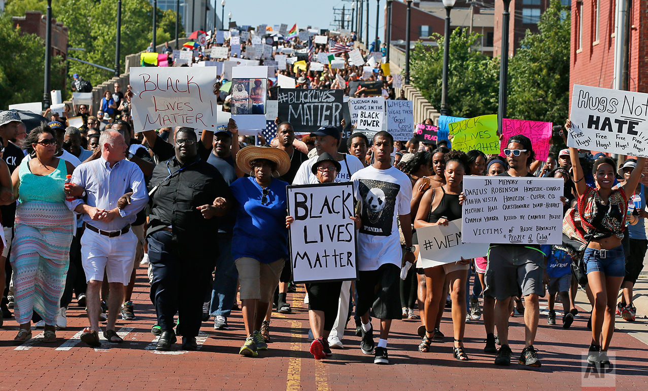 In this Sunday, July 10, 2016 photo, people march in a Black Lives Matter rally in Oklahoma City.(AP Photo/Sue Ogrocki)