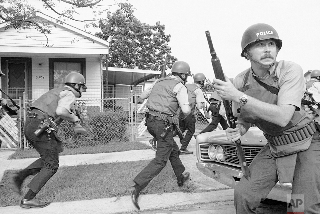 New Orleans police officers try to keep their heads down as they move in on a Black Panther headquarters during an exchange of gunfire in New Orleans on Sept. 15, 1970. (AP Photo/Jack Thornell)