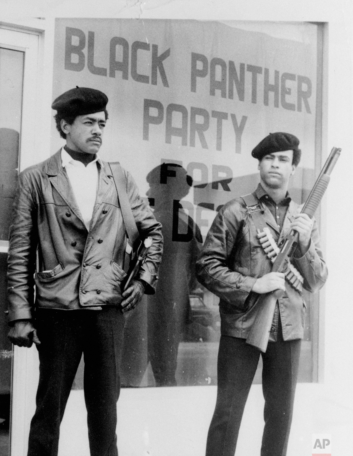 In this undated photo, Black Panther national chairman Bobby Seale, left, wearing a Colt .45, and Huey Newton, right, defense minister with a bandoleer and shotgun are shown in Oakland, Calif. Hundreds of former Black Panthers from around the world are expected to gather in Oakland, Calif., for a four-day conference that started Thursday, Oct. 20, 2016. (The San Francisco Examiner via AP)
