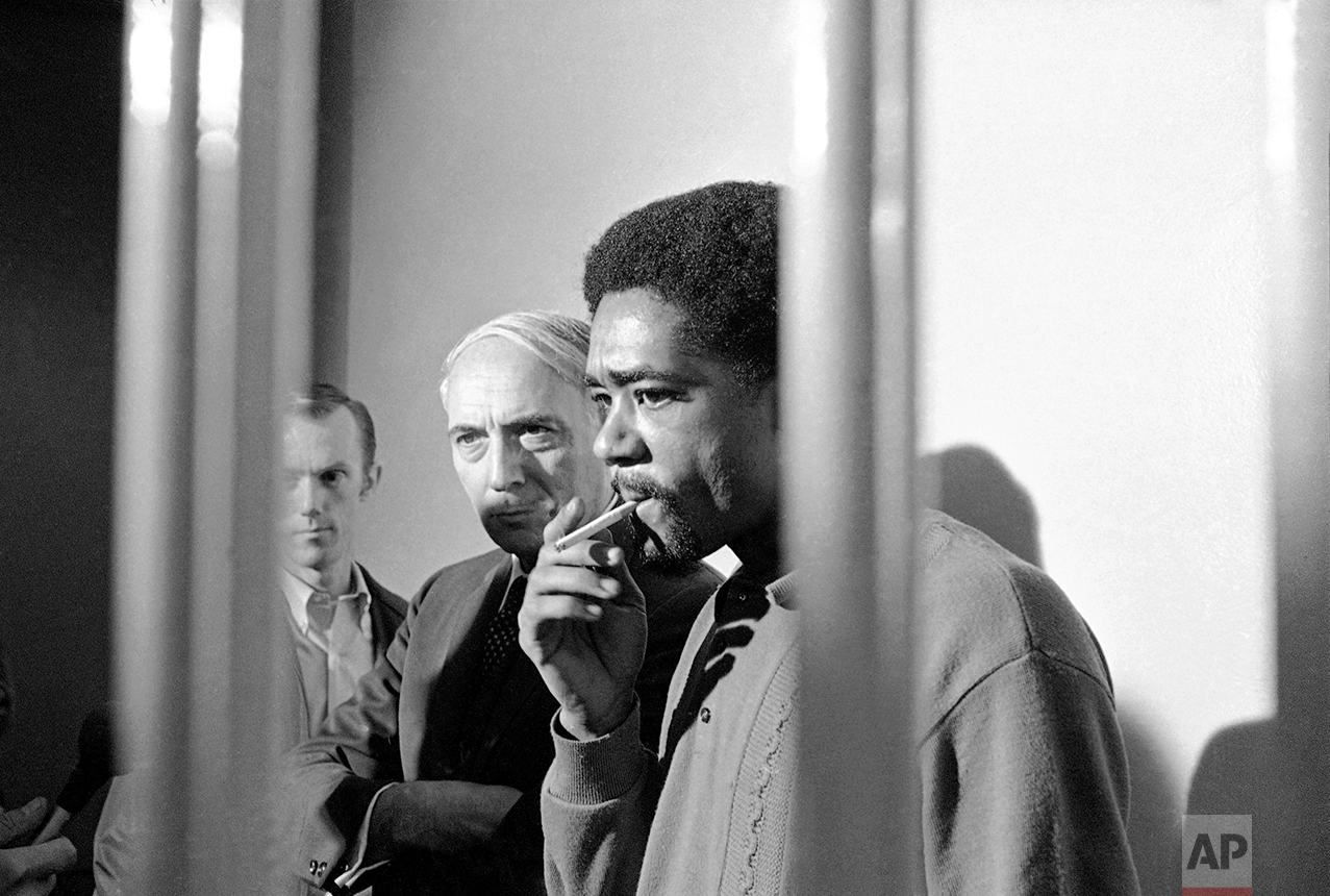Standing in the visiting cell of the San Francisco City Prison, Bobby Seale, Black Panther leader, puffs on a cigarette during an informal news conference on Monday, Nov. 11, 1969 in San Francisco. Seale was returned to San Francisco from Chicago where he was sentenced to four years in jail on contempt of court charges. Seale was one of eight defendants charged with conspiracy in connection with the 1968 Democratic Convention riots in Chicago. Standing beside Seale is his attorney Charles Garry who could not represent him in Chicago because he had undergone surgery. (AP Photo)