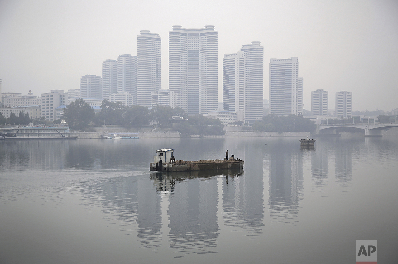 Residential buildings along Changjong Street which form part of the Pyongyang skyline are reflected in the Taedong River on a misty morning on Sunday, Oct. 16, 2016, in Pyongyang, North Korea. (AP Photo/Wong Maye-E)