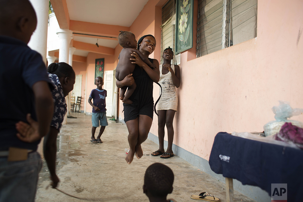 A girl holds a baby as she jumps rope at a school where people have taken refuge after losing their homes to Hurricane Matthew in the village of Mersan in the Camp-Perrin district of Les Cayes, Haiti, Sunday, Oct. 16, 2016. Aid workers who specialize in working with children in crisis say they fear kids will struggle with emotional aftershocks of the violent storm. (AP Photo/Dieu Nalio Chery)