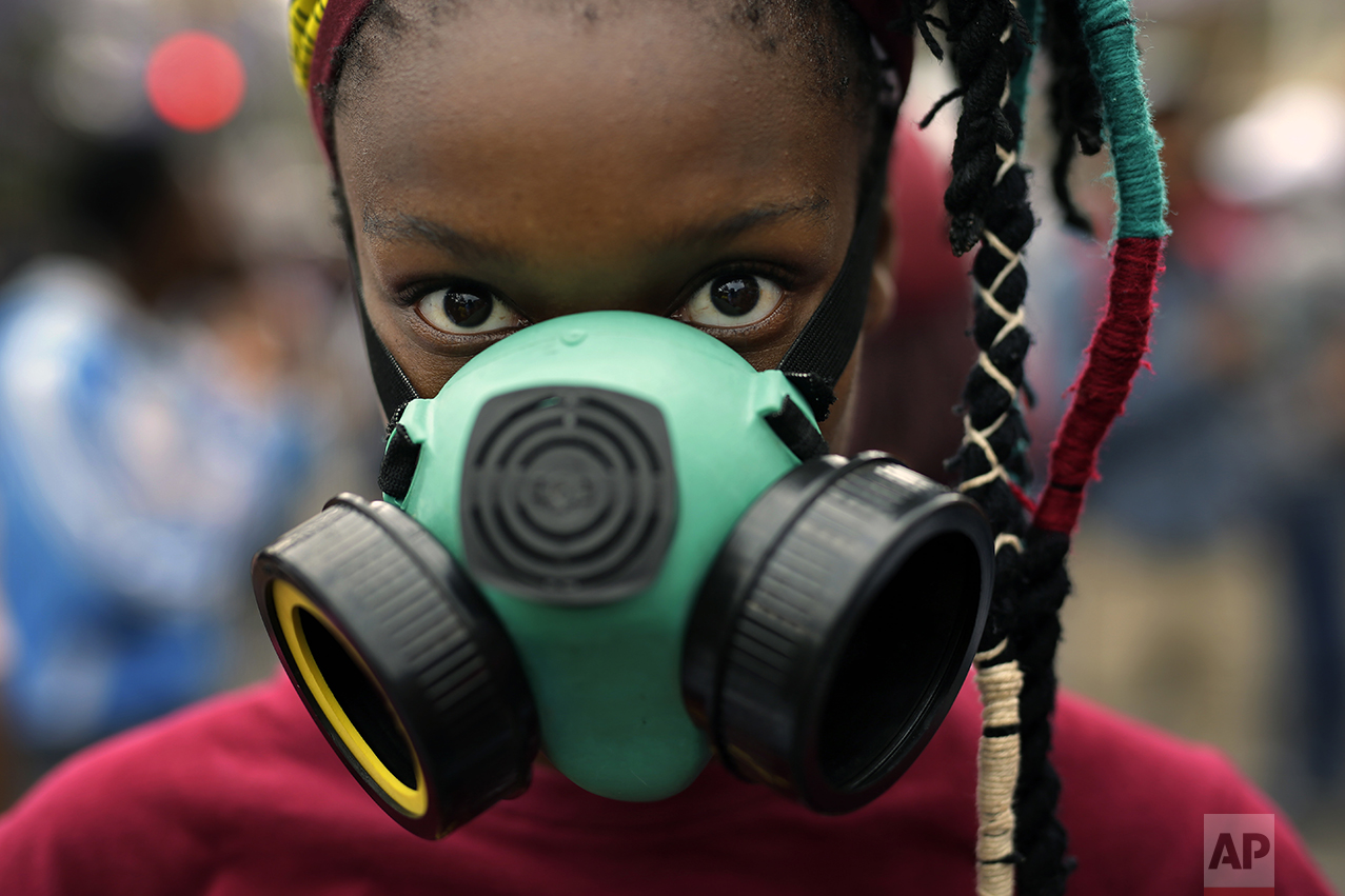 A student wears a mask as she and others demonstrate in downtown Pretoria, South Africa, Thursday, Oct. 20, 2016. The students were granted last minute permission to walk to the Union Building. Protests calling for free education have sometimes turned violent, and have affected many South African universities since last month. (AP Photo/Jerome Delay)