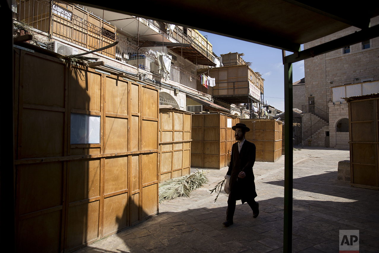 An ultra-Orthodox Jewish man walks next to sukkahs, temporary structures built for the Jewish holiday of Sukkot, in Jerusalem, Sunday, Oct. 16, 2016. The huts commemorate the temporary, portable dwellings in which Jewish people lived during their 40-year sojourn in the wilderness that followed their liberation from slavery in Egypt. (AP Photo/Sebastian Scheiner)