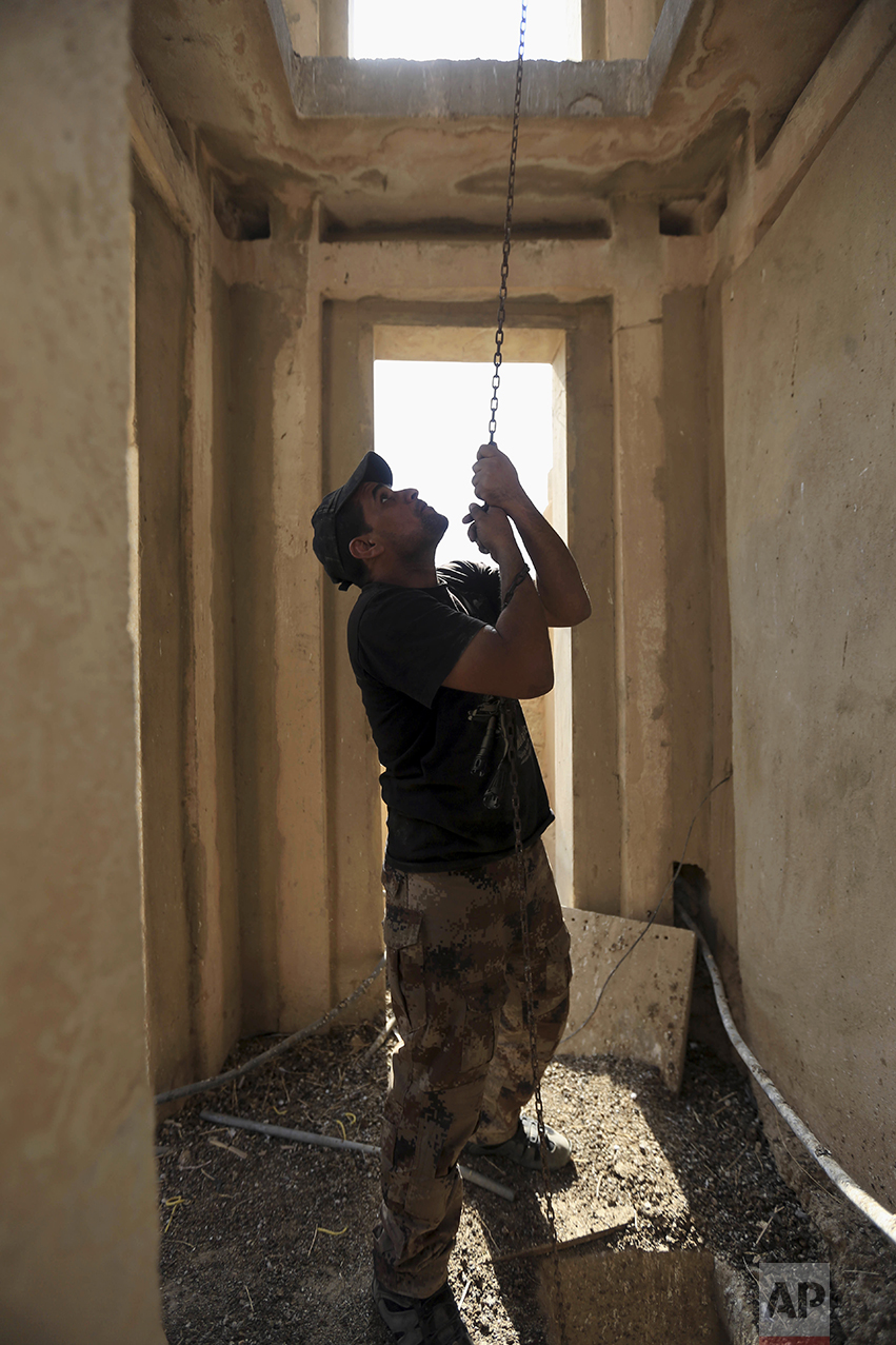 A member of Iraq's elite counterterrorism rings the bell in the church of Saint Shmoni, damaged by Islamic State fighters, in Bartella, Iraq, Sunday, Oct. 23, 2016. Iraqi forces captured Bartella, around 15 kilometers (9 miles) east of Mosul. (AP Photo/Khalid Mohammed)