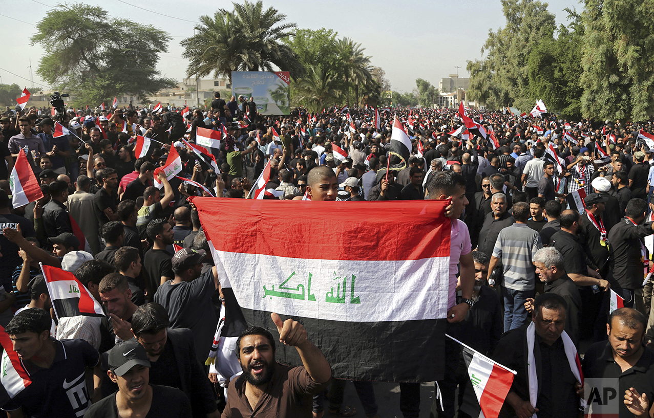 Supporters of Shiite cleric Muqtada al-Sadr wave national flags during a demonstration in front of the Turkish Embassy calling for the immediate withdrawal of Turkish troops from northern Iraq, in Baghdad, Iraq, Tuesday, Oct. 18, 2016. Thousands of followers of al-Sadr are demanding the withdrawal of Turkish troops from a base near the northern city of Mosul. Turkey says the troops are training Iraqi fighters to help retake Mosul from the Islamic State group, and that they are there with the permission of the Iraqi government. Baghdad denies it granted permission and has ordered them to withdraw -- a call Ankara has ignored. (AP Photo/Karim Kadim)