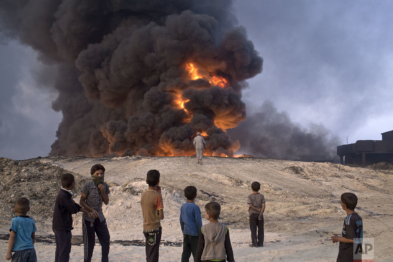 In this Sunday, Oct. 23, 2016 photo, people watch a burning oil well in Qayyarah, about 31 miles (50 km) south of Mosul, Iraq. In the week since Iraq launched an operation to retake Mosul from the Islamic State group, its forces have pushed toward the city from the north, east and south, battling the militants in a belt of mostly uninhabited towns and villages. In the heavily mined approaches to the city they met with fierce resistance, as IS unleashed suicide truck bombs, rockets and mortars. (AP Photo/Marko Drobnjakovic)