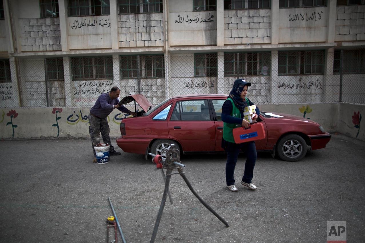 Jordanian plumber Maryam Mutlaq, 41, arrives to a school in Zarqa, northeast of Amman, Jordan, Monday, March 21, 2016. (AP Photo/Muhammed Muheisen)