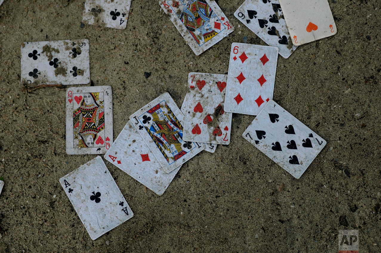 "In this Thursday, Oct. 27, 2016 photograph, playing cards lay abandoned outside a shelter in the makeshift migrant camp known as ""the jungle"" near Calais, northern France. (AP Photo/Matt Dunham)"