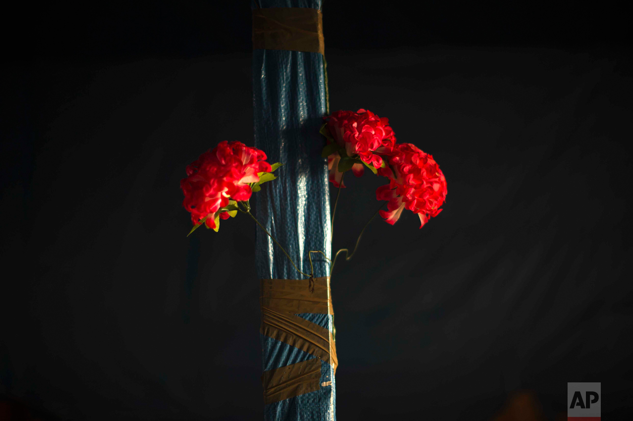 "In this Tuesday, Oct. 25, 2016 photo, plastic flowers are tied with tape to a pole of an abandoned tent at the makeshift migrant camp known as ""the jungle"" near Calais, northern France. (AP Photo/Emilio Morenatti)"