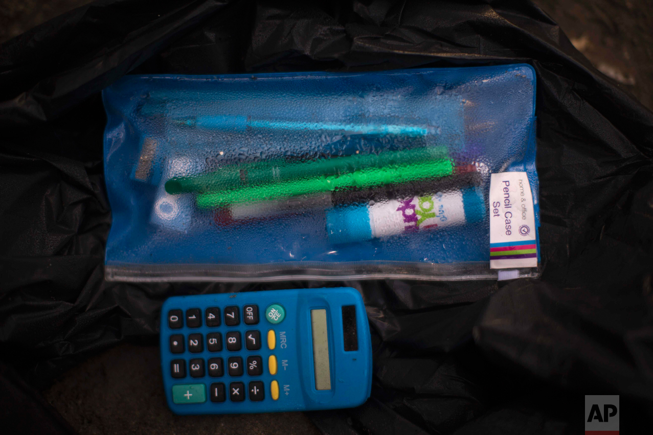 "In this Thursday, Oct. 27, 2016 photo, a case containing pencils next to a calculator left behind by migrants in an abandoned tent at the makeshift migrant camp known as ""the jungle"" near Calais, northern France. (AP Photo/Emilio Morenatti)"