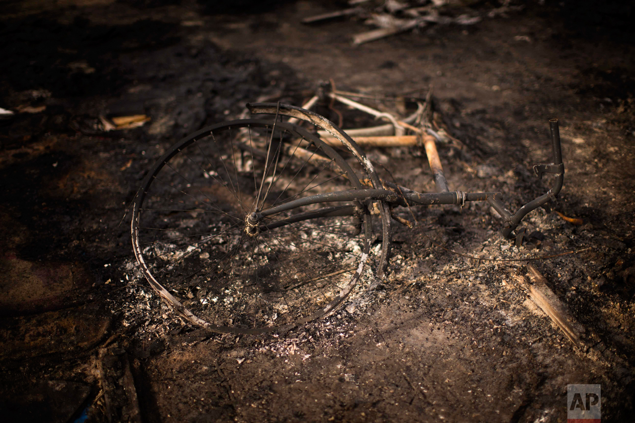 "In this Thursday, Oct. 27, 2016 photo, a burnt bicycle remains on the floor of a charred tent at the makeshift migrant camp known as ""the jungle"" near Calais, northern France. (AP Photo/Emilio Morenatti)"