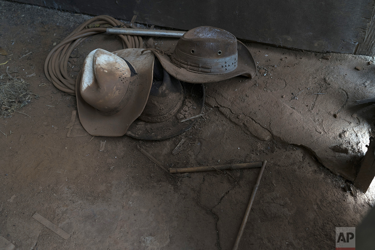 This Oct. 13, 2016 photo shows mud-caked hats in a home destroyed by a Nov. 5, 2015 mudslide unleashed by the bursting of a mine-waste basin, in Paracatu, Brazil. As much as people blame Samarco, the company behind the tragedy, they know mining has created thousands of jobs and provided millions in tax revenues, underscoring the influence that multinational corporations often have in otherwise rural and poor areas where they operate. (AP Pghoto/Leo Correa)