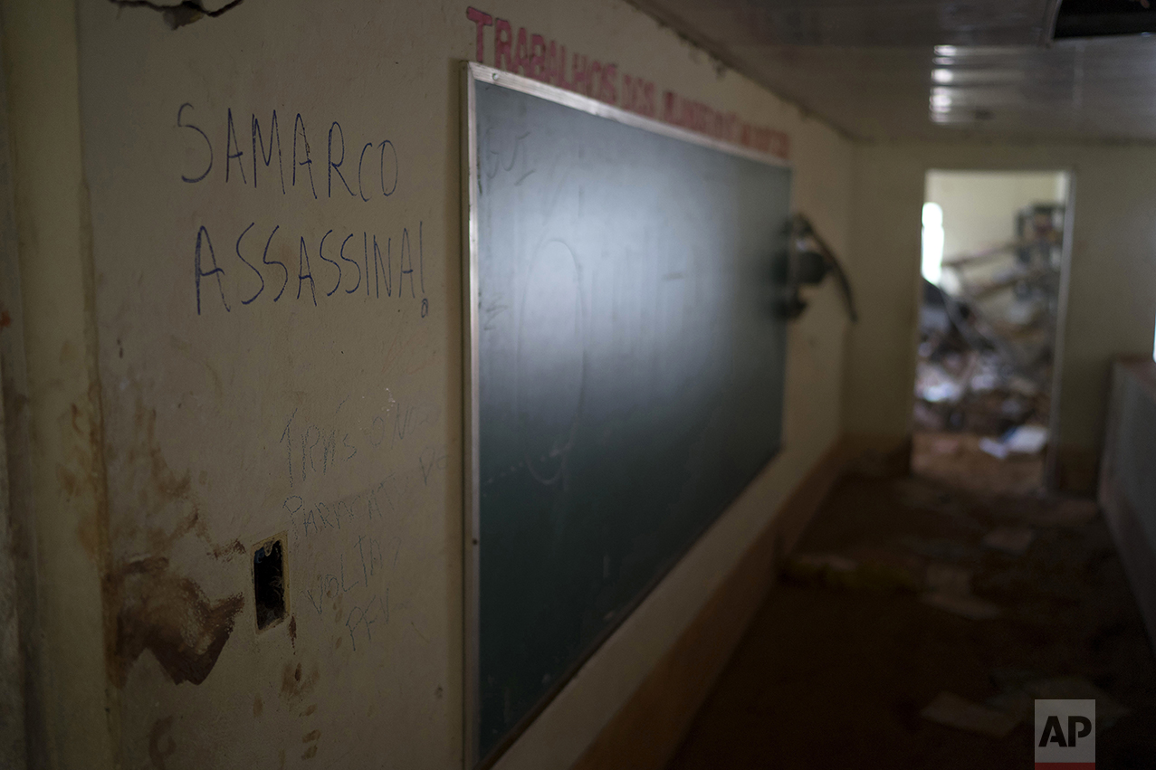 """This Oct. 13, 2016 photo shows a scrawled message in Portuguese that reads; """"Samarco Assassin!"""" on a classroom wall at a school destroyed by a tsunami of mud, triggered on Nov. 5 2015, by the failing of a dam of a nearby iron mine, in Paracatu, Brazil. One year later, families whose lives were upended by the ravaging flood say they feel betrayed by the company behind it - Samarco, a joint venture of mining giants Vale of Brazil and BHP Billiton of Australia. (AP Photo/Leo Correa)"""