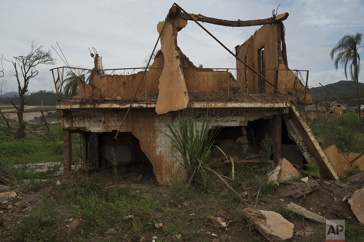 This Oct. 14, 2016 photo shows a home destroyed by a mudslide triggered by the Nov. 5, 2015 failing of a dam holding back a giant pond of mine waste, in Bento Rodrigues, Brazil. A year later the entire village is still brushed the color of clay. (AP Photo/Leo Correa)