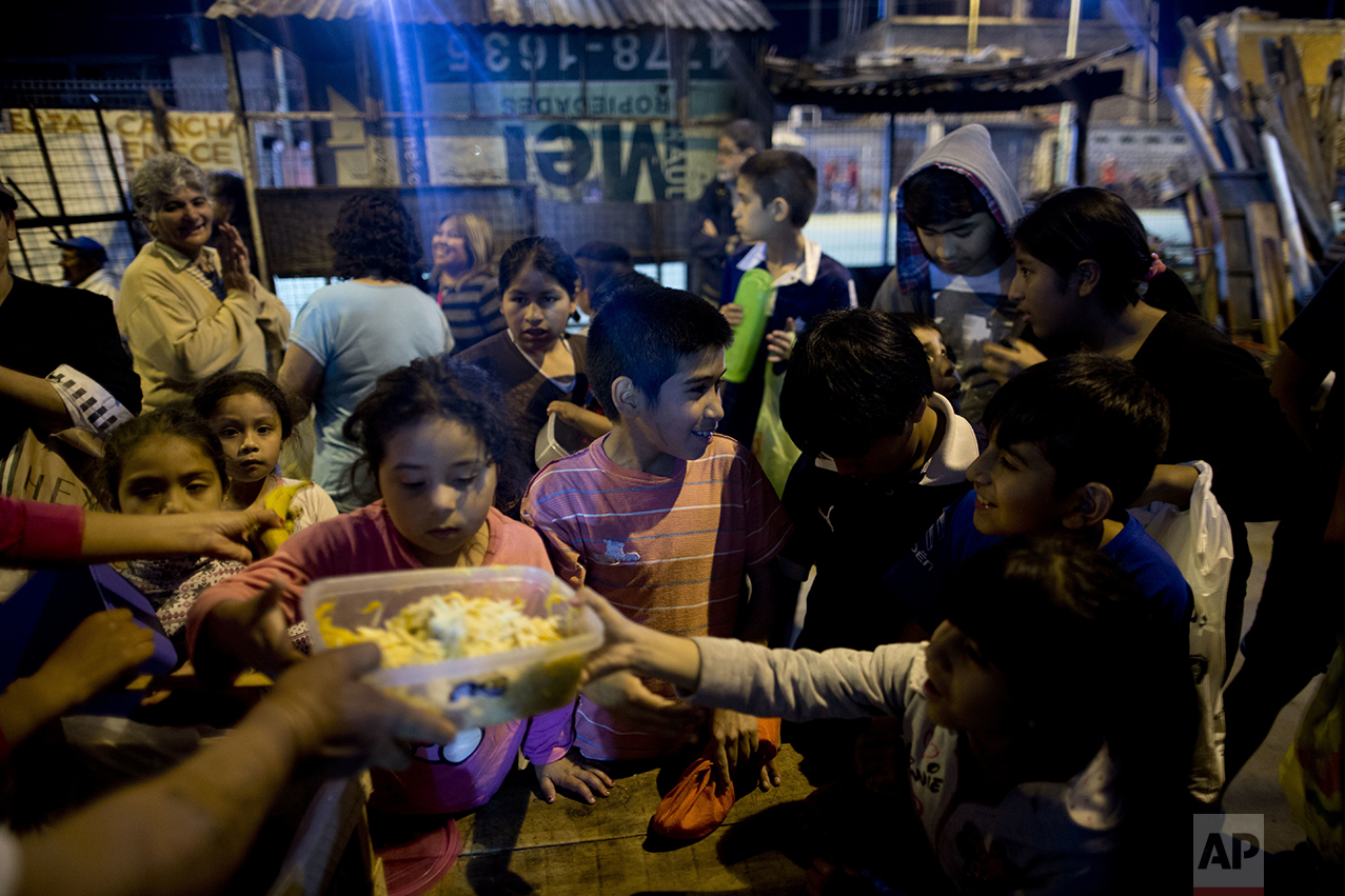 """In this Oct. 13, 2016, children gather for free food given out by Norma Colque at her soup kitchen in the Villa 31 neighborhood of Buenos Aires, Argentina. """"There's food for everyone. Don't worry,"""" Colque said as she dumped ravioli into the containers that the families would carry back to their homes. But Colque worries that may not be true for long. (AP Photo/Natacha Pisarenko)"""