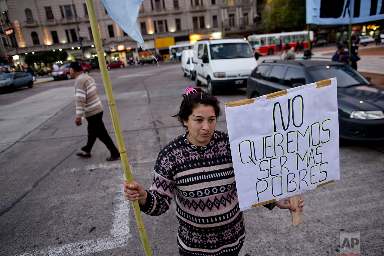 """In this Oct. 5, 2016 photo, Ana Paz holds a sign that reads in Spanish """"We don't want to be poorer"""" as she protests outside Congress, near a soup kitchen in Buenos Aires, Argentina. President Mauricio Macri's market-friendly reforms have been praised by international investors, who say they lay the groundwork for growth. But so far, they've brought only pain to the country's poor. (AP Photo/Natacha Pisarenko)"""