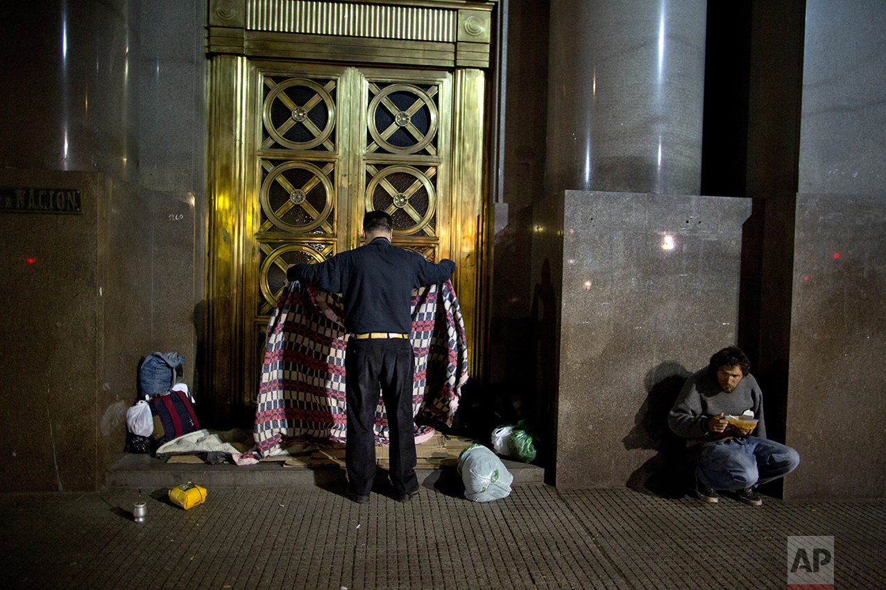 """In this Oct. 5, 2016 photo, Alberto Cejas, who said he became homeless three years ago, prepares a place to sleep on a bed of cardboard outside the Senate Library in Buenos Aires, Argentina. As President Mauricio Macri campaigned last year, he often said his goal was to reach """"zero poverty"""" by the end of his term in 2019. But when he released the poverty figures in late September, he said it's obvious it won't be possible. (AP Photo/Natacha Pisarenko)"""
