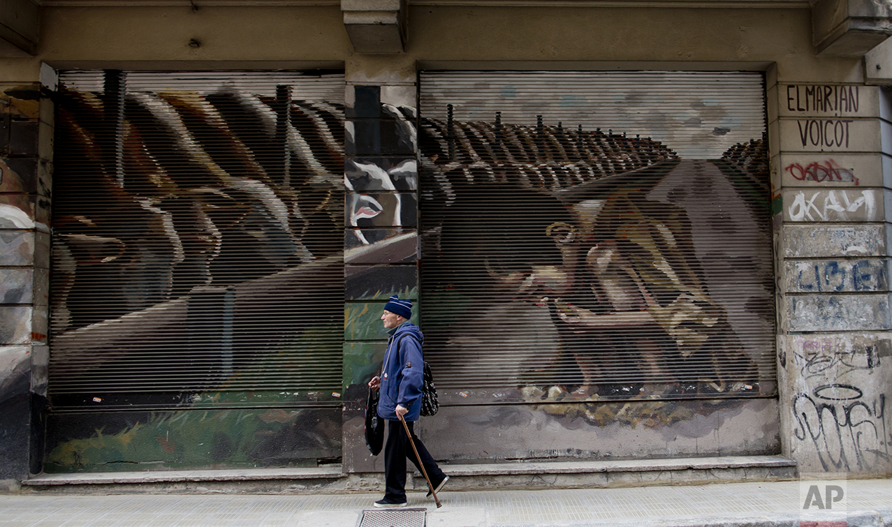 """This Oct. 5, 2016 photo shows a mural titled """"Hunger Games"""" by artist El Marian, featuring a starving boy huddling next to cattle eating grain in Buenos Aires, Argentina. The mural was an idea from animal rights group """"Voicot"""" and aims to call attention to Argentina being one of the world's top grain producers, and that most of it is used to feed livestock. (AP Photo/Natacha Pisarenko)"""